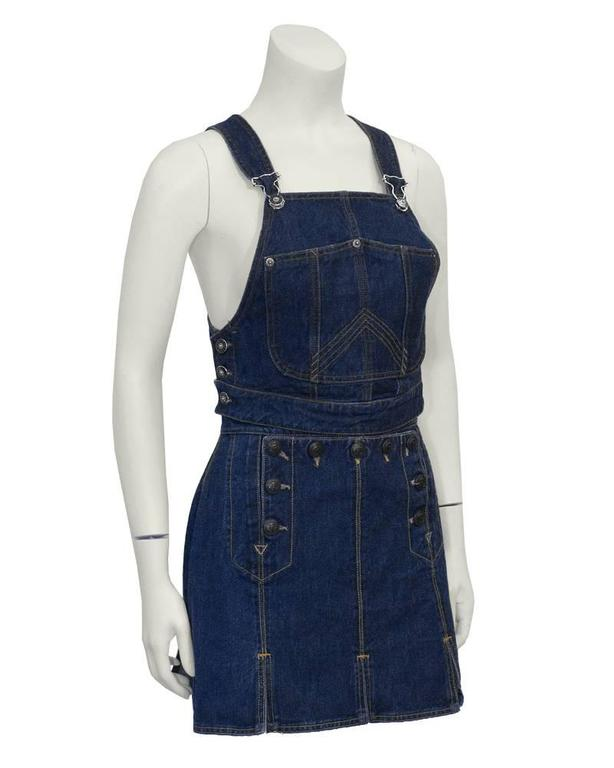 Unusual Jean Paul Gaultier denim 2 piece set from the early 1990's.  Cropped bib style overall top with adjustable shoulder straps and silver hardware. Three button closure on each side with custom buttons. Skirt has sailor-style drop flap with