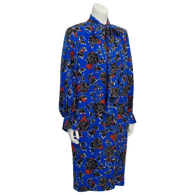 Amazing Yves Saint Laurent electric blue silk jacquard long sleeve dress  with sweet neck tie from the 1980s. Features a semi abstract rose pattern with notes of black, white, red and grey. Padded shoulders, and a v-neck with a long tie collar.