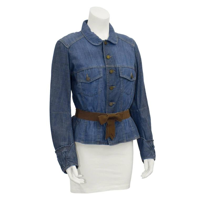Fabulous Alexander Mcqueen denim jacket from the early 2000's is a fresh twist on a staple piece. Features a peter-pan collar, and button closure down centre. Sleeves are loose fitting with an elasticized cuff. Waist is cinched and belted with a
