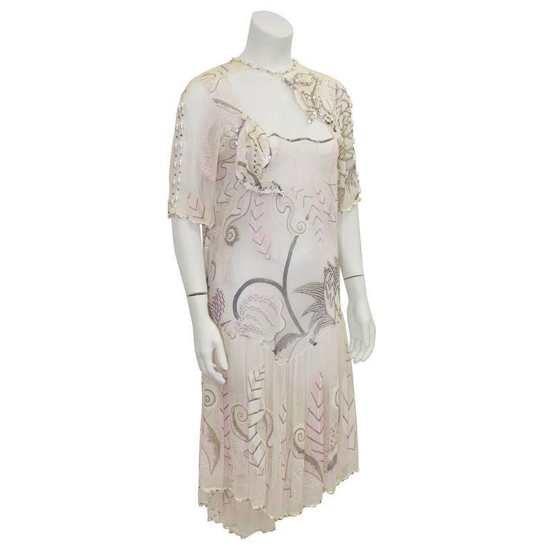 Stunning 1980's Zandra Rhodes light pink and cream hand painted silk chiffon dress. Sheer fabric on the decolletage with short sleeves. Pearl detailing along the neckline, sleeves and hem. Drop waist, with a very low cowl back. Renowned free hand