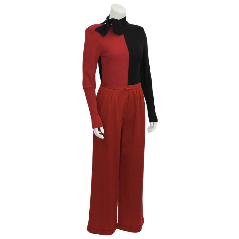 Make a fabulous statement with this Sonia Rykiel raspberry red and black knit ensemble from the 1980s. Color block red and black knit sweater has an off set petite necktie, and long sleeves ribbed to the elbow. Back side is all black. Brilliant