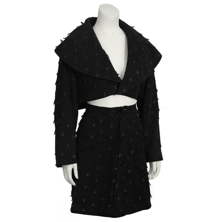 This chic Alaia black suede set from the 1980's features a cropped jacket, and mini skirt. Jacket has extended shawl style collar, and single front button closure. A-line mini wrap skirt has two slit pockets at the hips. Front button closure. Unique