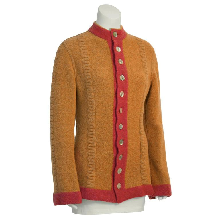 Stay warm and chic with this 1990's Alaia orange wool knit cardigan. Highly sought after early collection piece features orange boiled wool with salmon colored trim, high neck, and cable detail down front. Slightly flared wrists and nipped at the