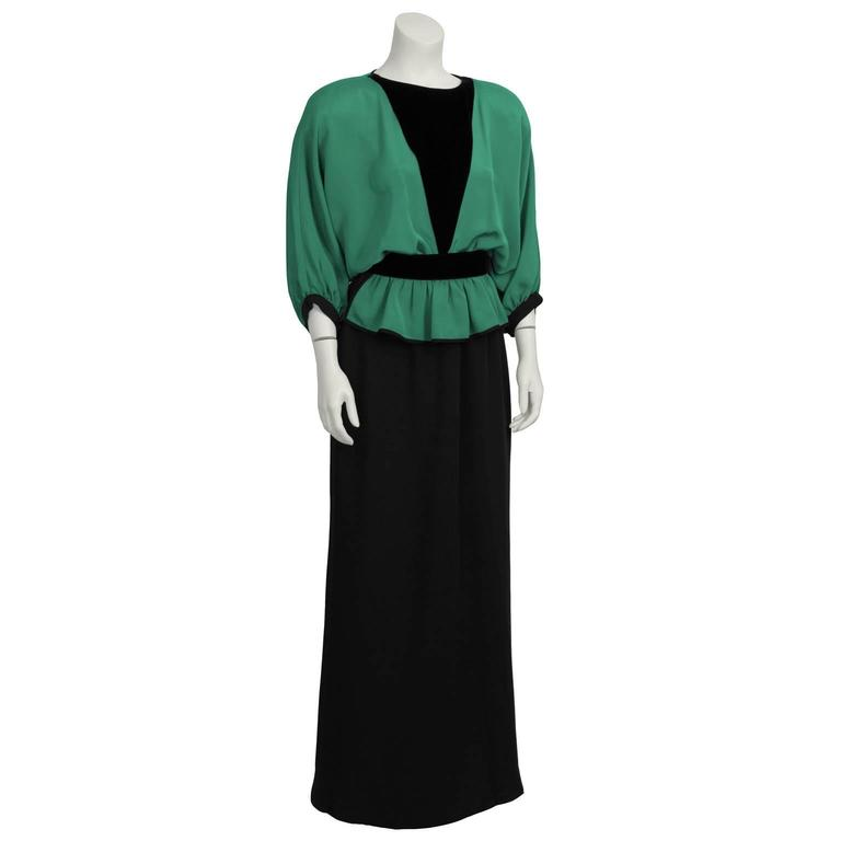 Fabulous green silk crepe and velvet black gown from Valentino from the 1990's features a  loose-fitting, green, bat wing sleeved bodice with a deep black velvet V in the center. Waist is cinched with gathering. Straight cut black skirt. Back single
