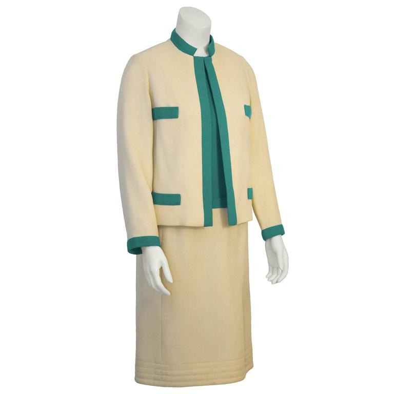 Chic 1960's Mary Korolnek cream and green raw silk dress and jacket ensemble. Jacket has green trim, four faux green flap pockets, and a single hook and bar closure. Classic Chanel inspired ladylike ensemble.  Sleeveless sheath dress has a green