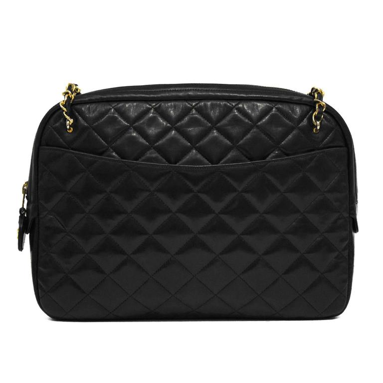 Classic 1980's Chanel black camera bag is made with black quilted lambskin, and features a large pocket on each sides, and a top zip closure. Chain straps have leather shoulder pads. Gold tone hardware. Excellent vintage condition. 