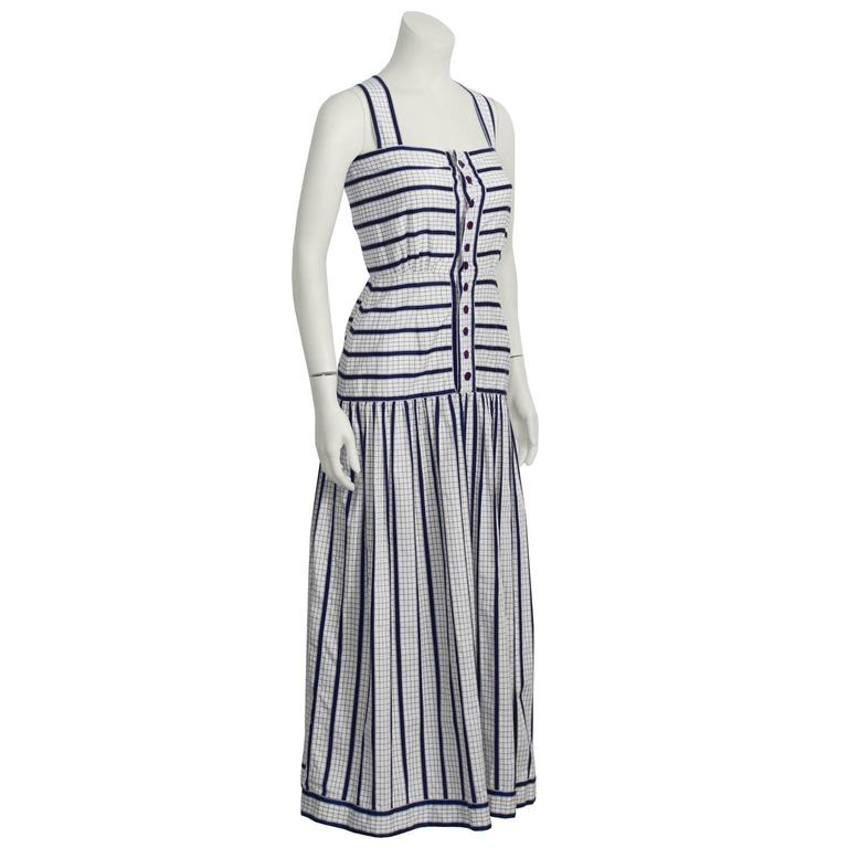 This 1970's Adele Simpson cotton maxi sundress is checkered white with navy stripes. Features a fitted waist, front button closure, and gathering at the hip set skirt. Excellent vintage condition. A wonderfully feminine and sweet summer item!  Fits