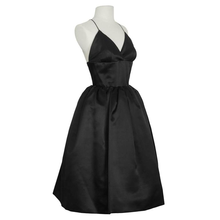 Norman Norell 1950's demi couture for I Magnin black satin cocktail dress with spaghetti strap plunging v neckline. Fitted bodice and pouf skirt with built in crinoline. Straps criss cross in the back, and fastens with two zippers and a waist