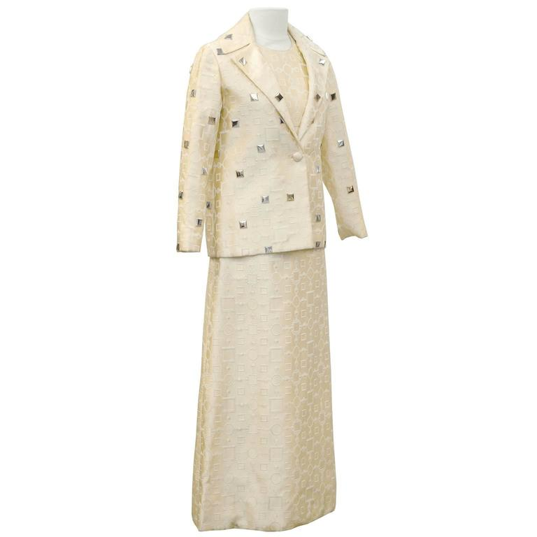 Anonymous cream brocade fabric featuring mod geometric print of circles and squares. High neck empire waist A-line sleeveless gown. Finished with a small notched lapel blazer of the same fabric. Single button closure decorated with gold and silver