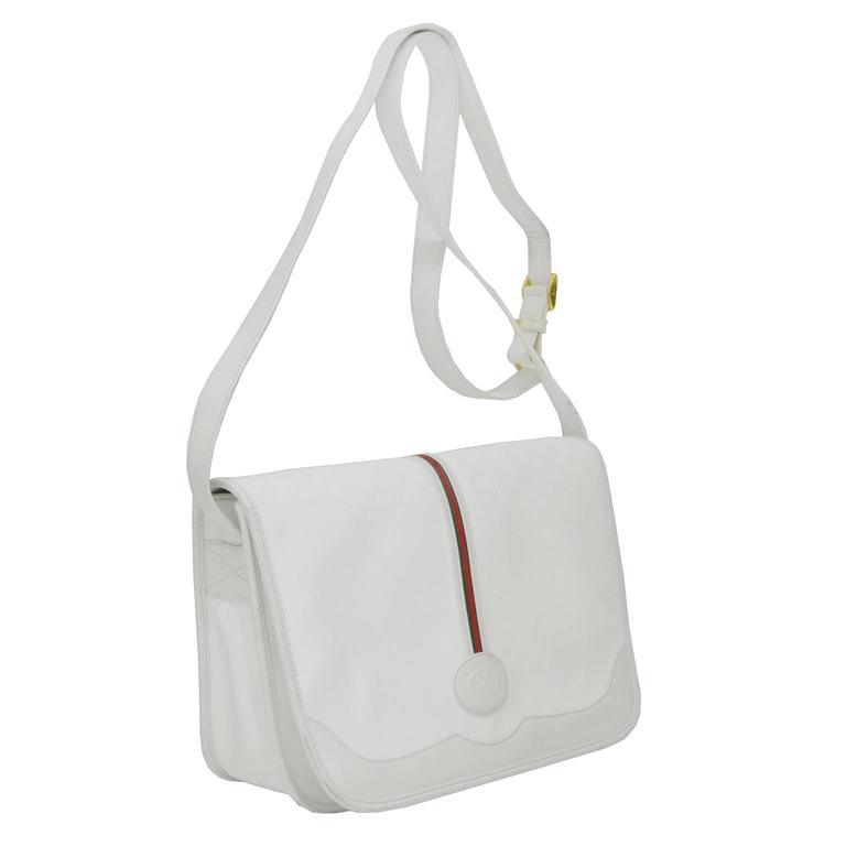 1970's Gucci white coated canvas and leather messenger bag with a long adjustable cross body strap. Constructed of grey on white signature monogram canvas trimmed in a smooth white leather. Large flap is decorated with a vertical red and green