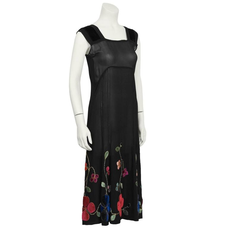 1930's black semi-sheer chiffon black tea/cocktail dress. The shift style dress has wide straps with velvet detail and lattice seaming down the front and back. The slightly flared skirt is embellished with hand sewn velvet floral embroidery in red,