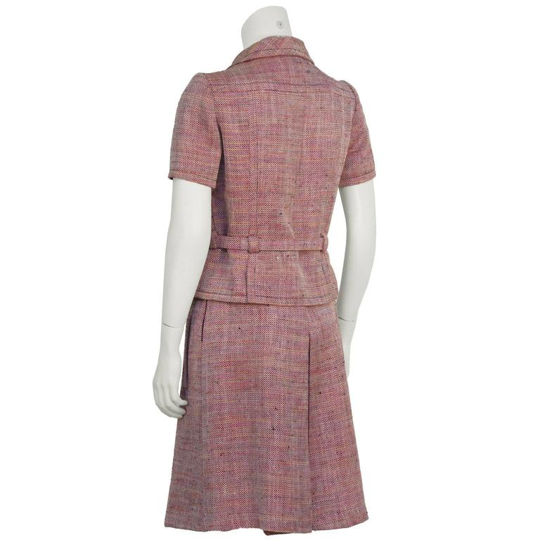 1960's Guy LaRoche red, pink, orange and blue rayon tweed short sleeved skirt suit. The jacket features a fully adjustable belt at the waist with pewter metal buttons down the front. Skirt has an inverted pleat on the front and back and two banded