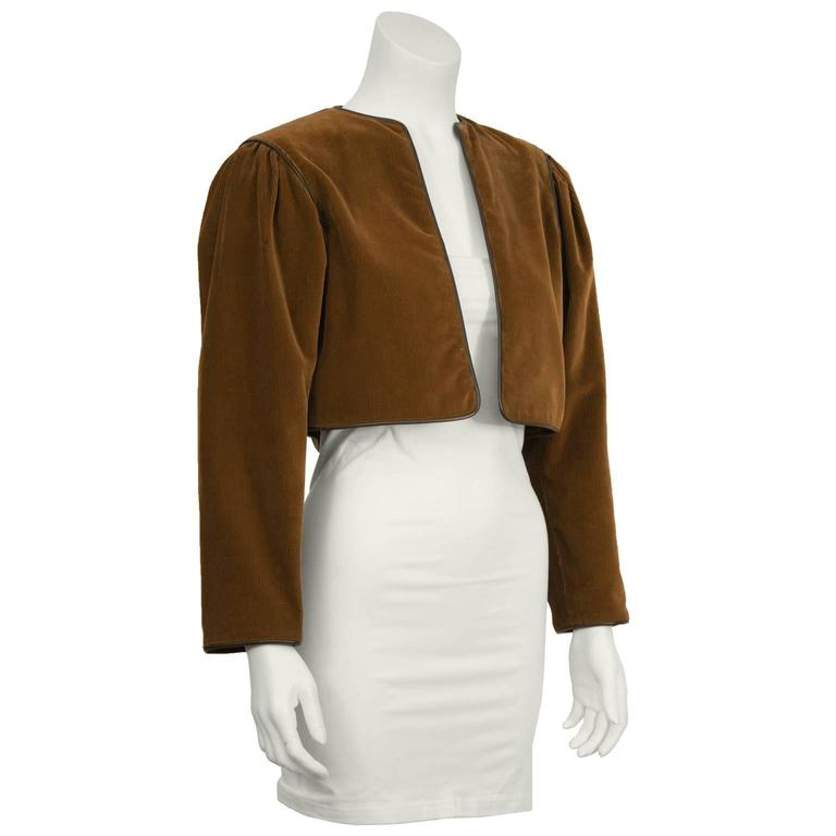 1970's iconic Yves Saint Laurent cropped brown corduroy bolero jacket with dark brown leather piping. Slight gathering at shoulder and lined in brown satin. In excellent condition. Fits like a US size 2-4.
