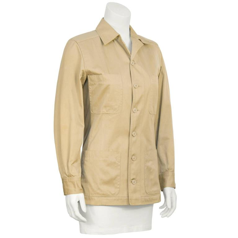 1990's Yves Saint Laurent Rive Gauche safari style jacket in cotton khaki. The jacket buttons down the front and features four pockets at the breast and at the hips, finished with a buttoned barrel cuff. In excellent condition. Fits like a US 4.