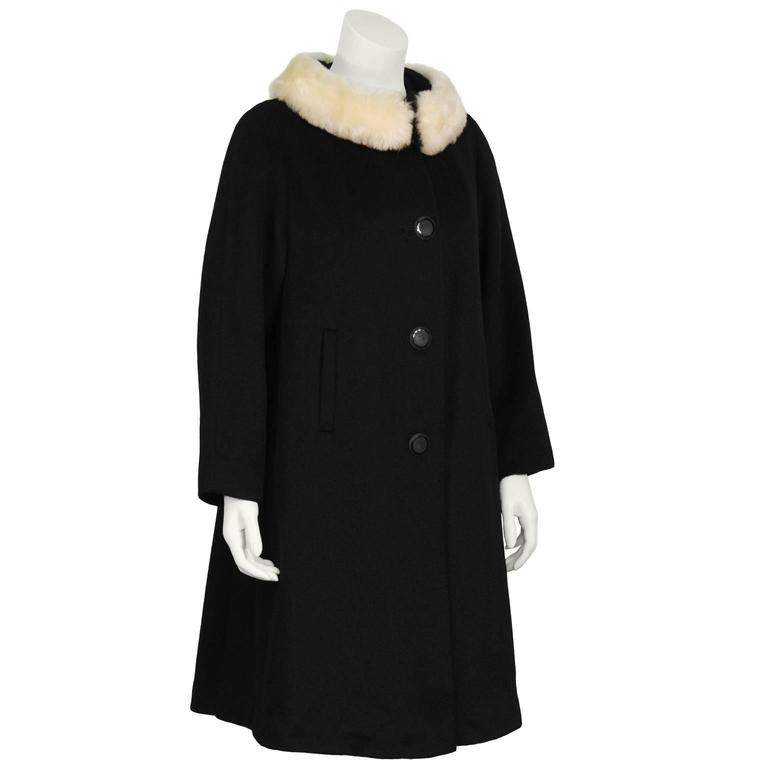 Lilli Ann 1960's black wool swing coat with a cream faux fur detail at neck. The coat does up the front with large black circular buttons and the faux fur collar closes with large hook and eyes. Features two side slit pockets Still stitched close