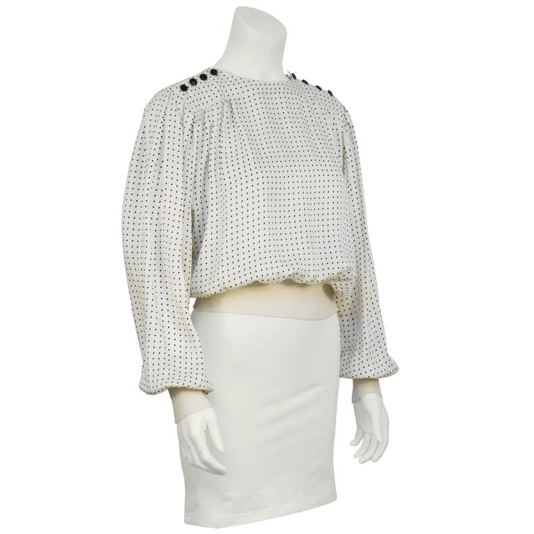 Emanuel Ungaro off white and black silk polka dot blouse from the 1980's. The blouse features a yoke neckline with four black faceted round buttons on either shoulder. The hem and cuffs are finished in cream ribbed knit. The top has pleating along