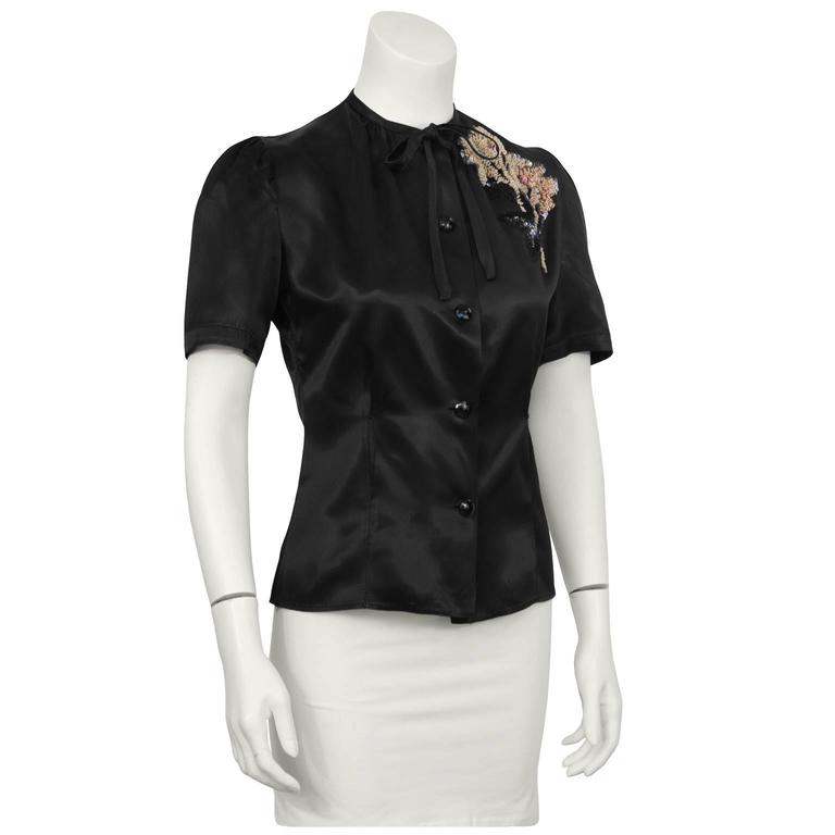 The best 1940's satin black fitted blouse with hand sewn sequin bouquet appliqué. The blouse features a skinny self tie bow and jet black faceted buttons down the front with a feminine puff sleeve. Fitted through the waist. In excellent condition.