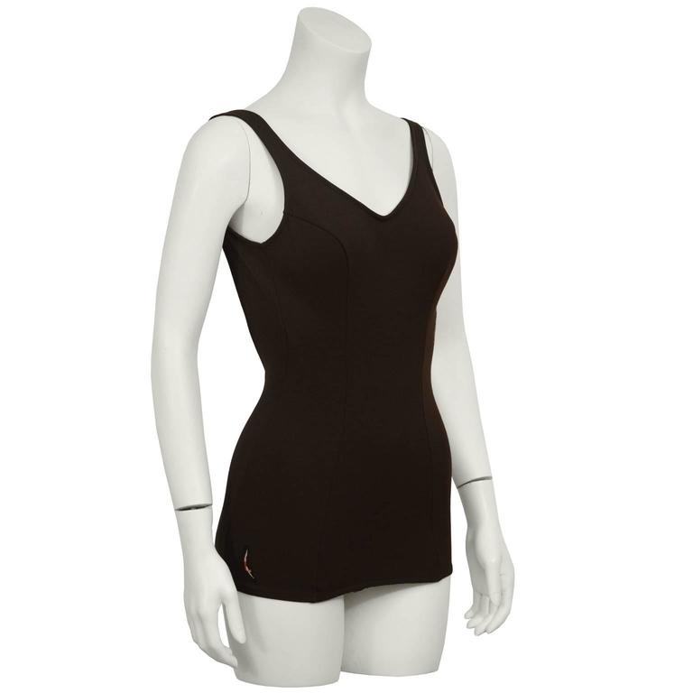 Classic Jantzen brown one-piece stretch polyester bathing suit from the late 1960's. Features a sewn in bra with cups and a low back, seams down the front. Finished with a Jantzen diving girl logo patch on the left hip. Elastic and synthetic fabric