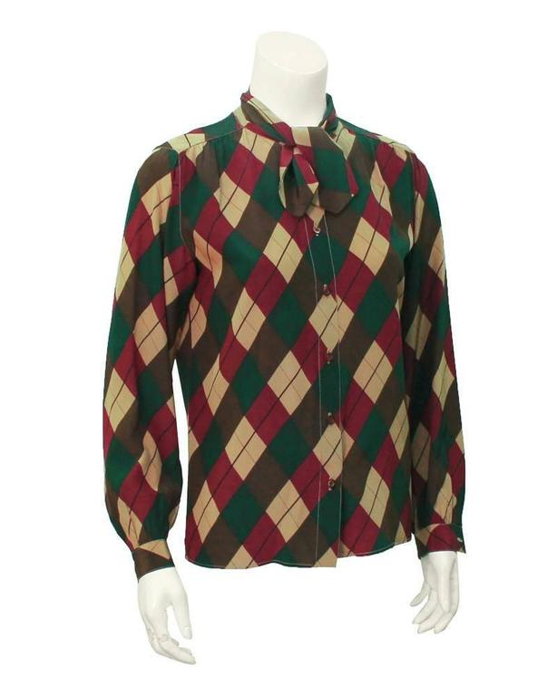 1970's silk Tiktiner argyle blouse in hunter green, brown, tan and maroon. Matching tan stitching throughout seams. Short tie at the neck and brown buttons down the front. Color combination is perfect for a preppy fall look. In excellent vintage