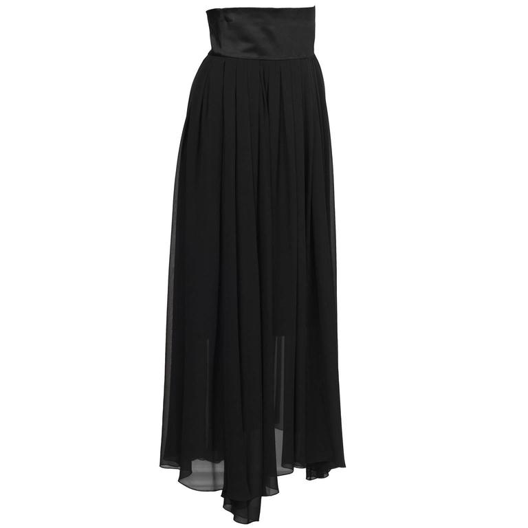Chanel 1980's black crinkle chiffon and satin evening skirt. The skirt is composed of two layers, the bottom one hits at below the knee and is pencil skirt style, while the over skirt is loosely gathered and flows to the ground. Finished with a wide