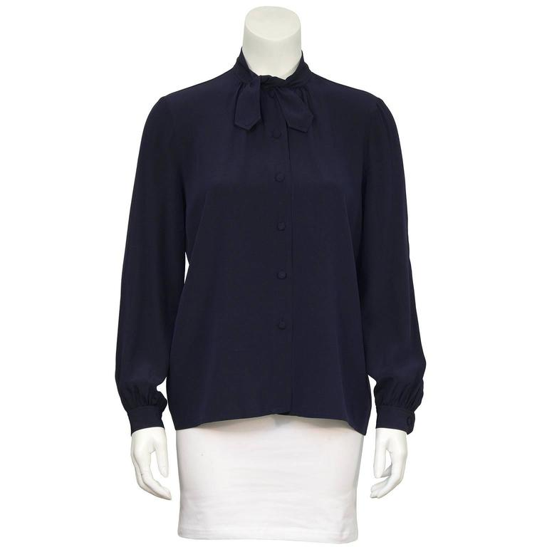 1970's navy silk blouse labeled Chanel Creations. The blouse has a short tie at the neck and buttons up the front with matching fabric covered buttons. The sleeves have a slight puff at the buttoned cuff. In excellent condition, fits like a US 4.