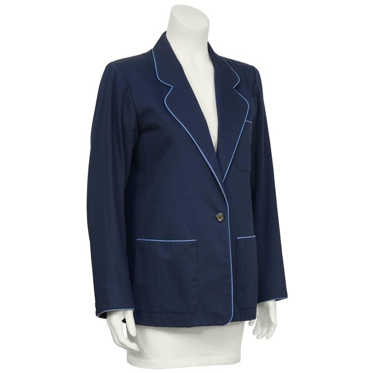 "Yves Saint Laurent ""menswear look"" tailored navy cotton twill jacket from the 1970's. Cut for a female figure with just a hint of schoolboy charm. The jacket has light blue piping along the pockets, cuffs and trim. Fastens with a single navy button"