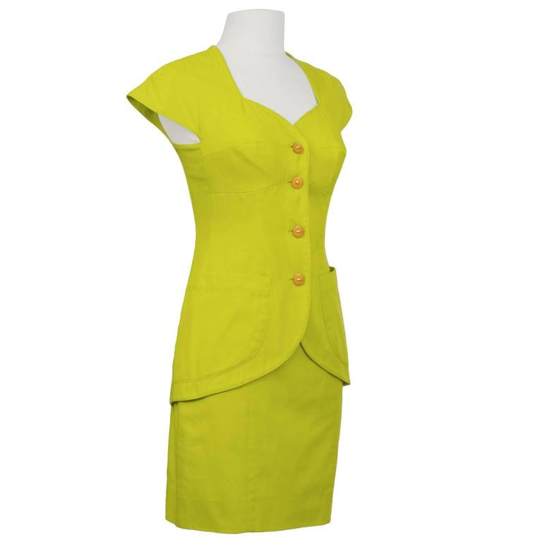 Well known 1980's Italian label Byblos chartreuse cotton jacket and skirt set. Dramatic sweet heart neckline with capped sleeves, long line jacket with descending curve to the hem and 2 patch pockets. Interesting body con stitching on jacket