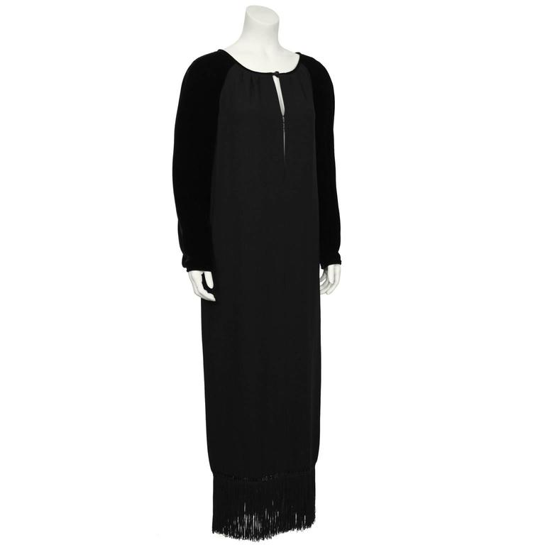 Gorgeous black velvet and crepe Valentino gown from the 1980's. The gown has a slit neckline that fastens at the center with invisible hooks and a faceted black jet button. The neckline is piped in black velvet that blends into the black velvet