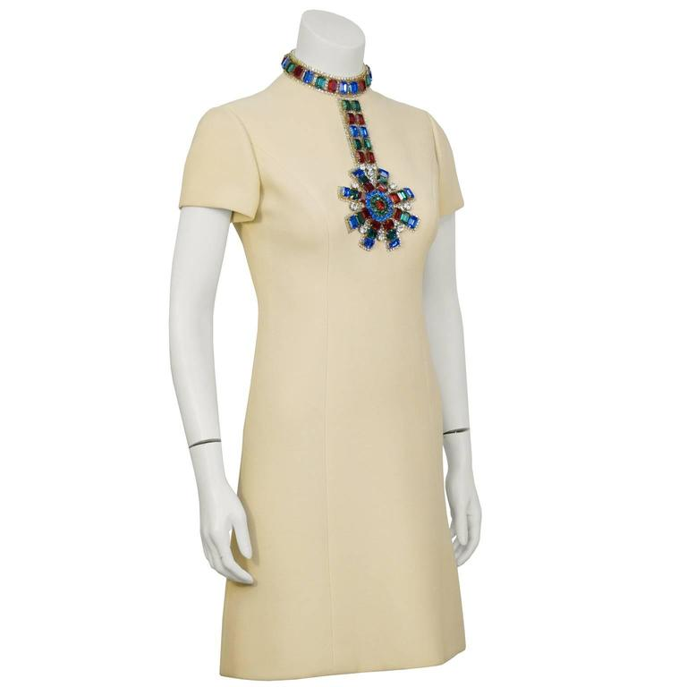 A stand out piece from the 1960's, this Norell off white cocktail dress with large jewel embellishment needs no accessories.  The classic A line shaped dress, made from mid weight wool. The high neckline and front bodice is adorned with large green,