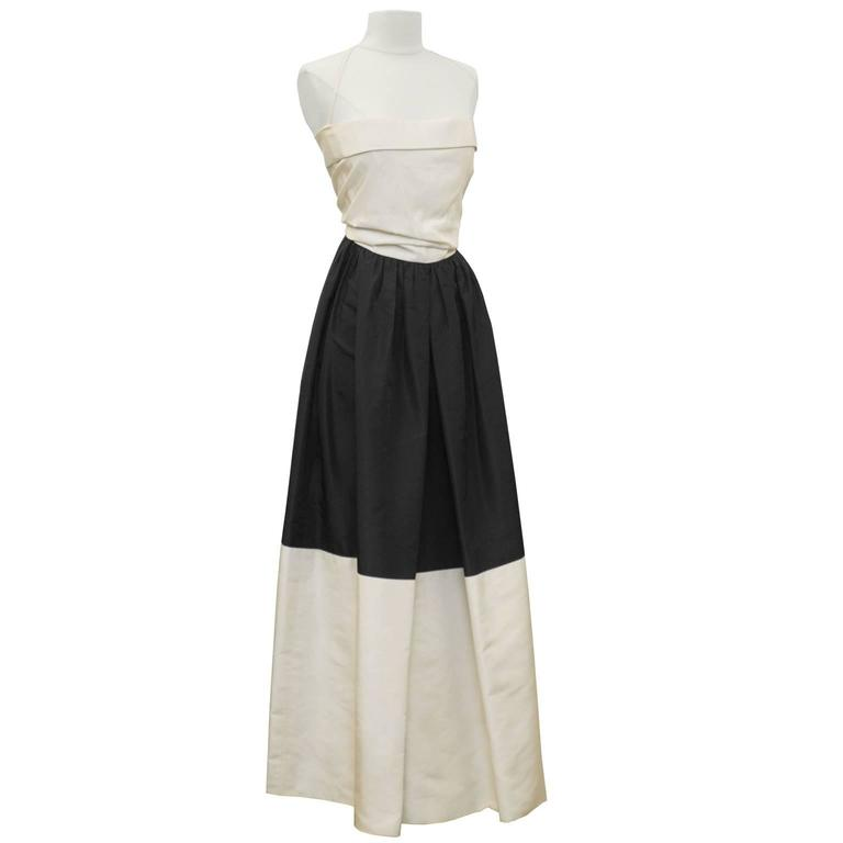 Elegant early 1960's black and cream silk taffeta strapless gown by Pauline Trigere. The gown is colorblocked with a cream bodice, black top skirt and cream hem. The top of the bodice has a single fold all around and there is a halter style strap