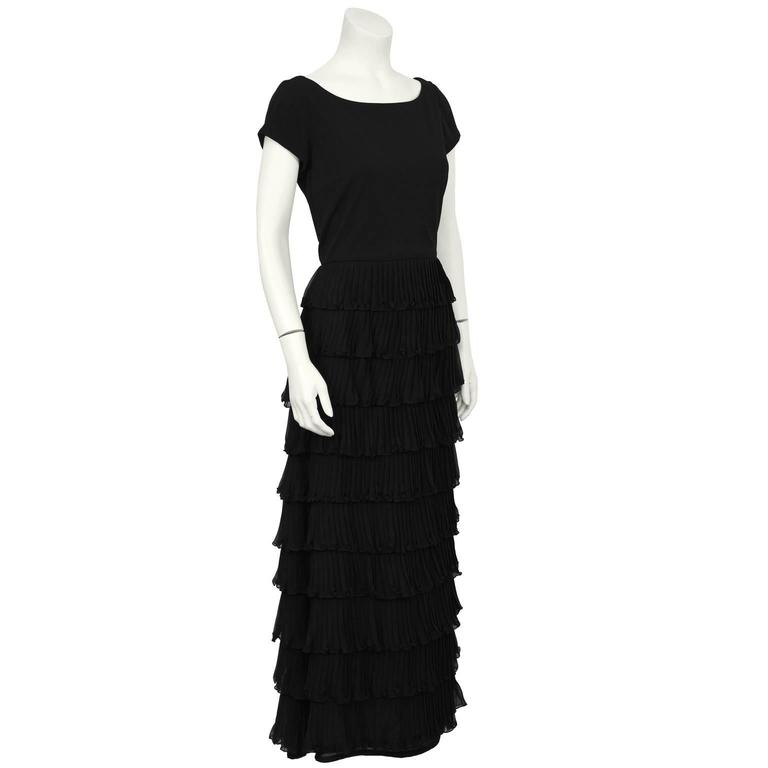 Black chiffon cap sleeved tiered gown from the 1980's. The gown has a scoop neckline and the skirt is made up of tiers of pleated chiffon. Zips up the back, lined in black polyester blend. In excellent condition, fits like a US 6-8.