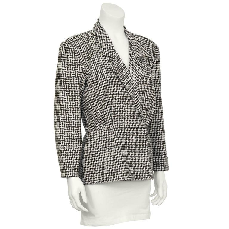 Unique fitted peplum style wool houndstooth check top from the first Michael Kors collection in 1981. The shirt style jacket has a retro 40's shape with an overlapping front that fastens on the inside with hidden flat hooks. Gathering at the bust,