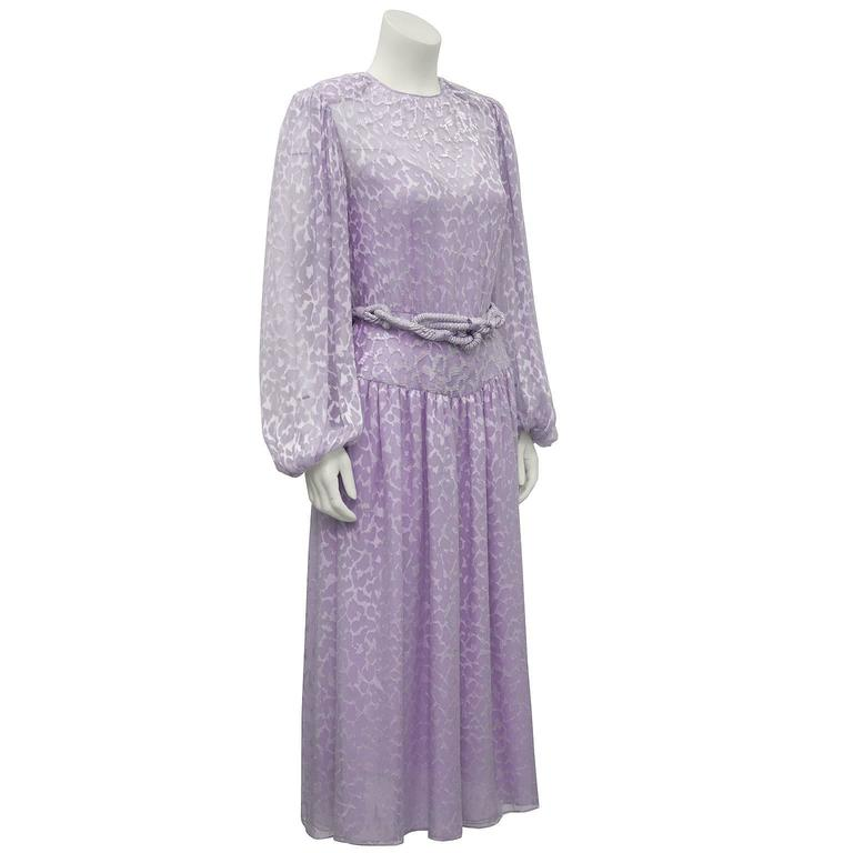 Lavender silk chiffon beaded evening dress by Oscar de la Renta. Fabric has an all over devoree leopard print with white iridescent beading at the neckline and along the waistband. Full sleeves with elasticized cuffs. Attached lavender slip and
