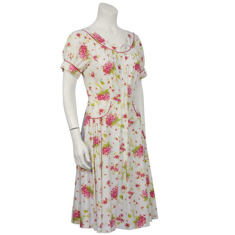 Green, pink and red floral printed cotton daydress from the 1950's. Red piping detail on the yoke style boatneck, cuffs and semicircle detail on hips. Zipper down the front is hidden behind a placket. Full skirt with pleating on hips, unlined. In