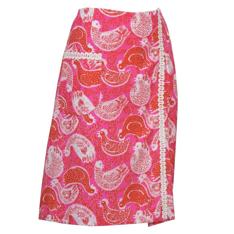 Pink and red rooster print Lilly Pulitzer wrap skirt from the 1960's. The skirt has one patch pocket on the front and white rickrack trim. In excellent, like-new condition, fits like a US 8-10.