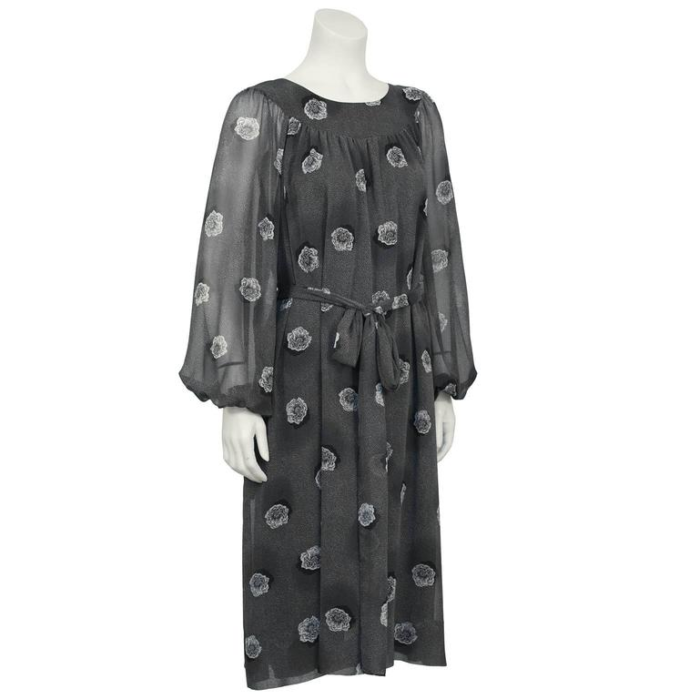 Loose fitting Hanae Mori gray printed chiffon dress from the 1970's. Yoke style neckline with see through chiffon Bishop style sleeves with elasticized cuffs. Dress features an allover gray speckled print with larger white and gray flowers. Dress is
