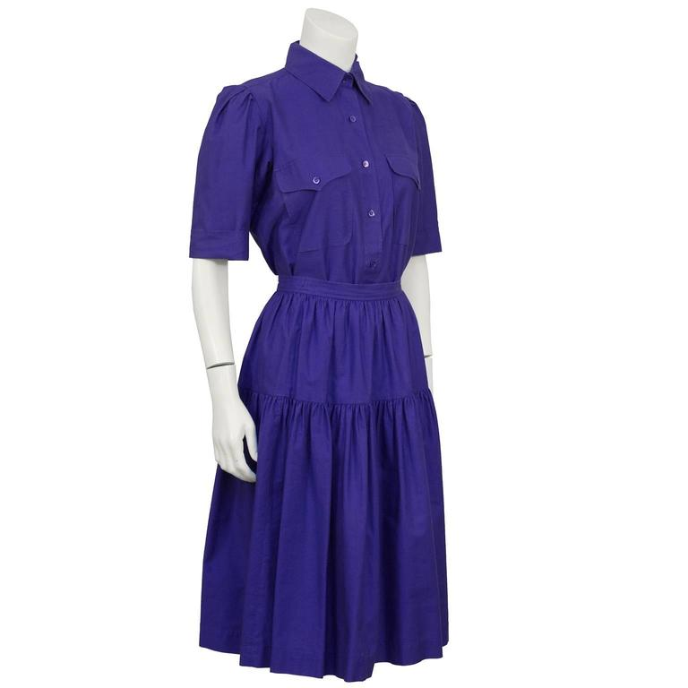 Purple cotton YSL skirt and button down ensemble from the 1970's. Collared shirt with small purple buttons down the front, top flap pockets on the bust and short sleeves. Yoke on the back, sleeves can be cuffed. Skirt has a banded waist, one tier