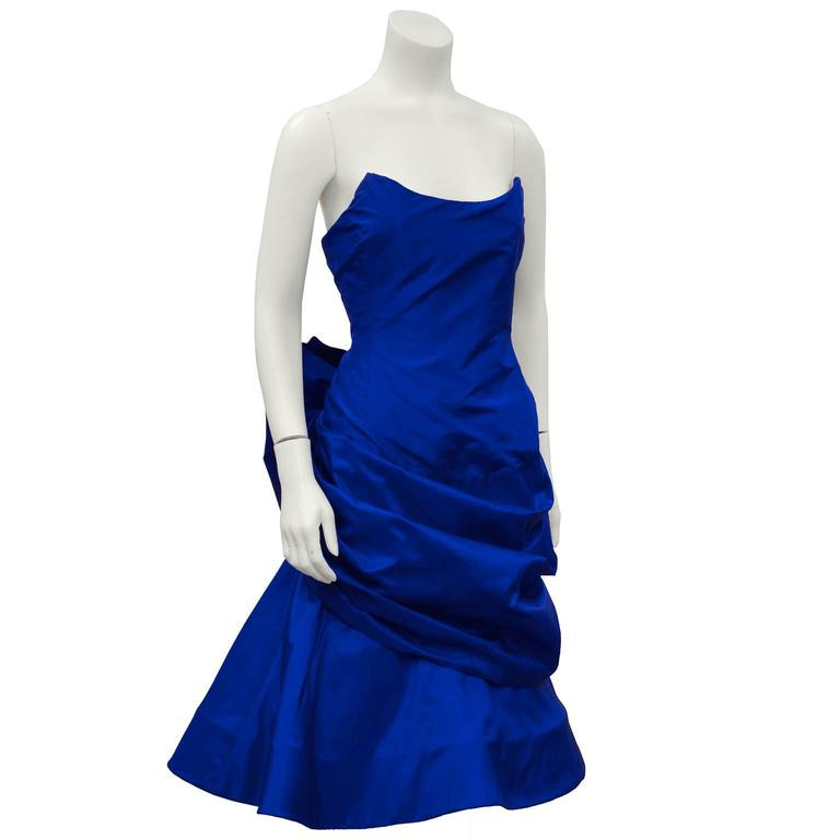 1980's royal blue silk taffeta fitted strapless cocktail dress by Arnold Scaasi. The neckline is very architectural and finishes with two points. The front is fitted across the bodice and gathers around the hips while the bottom skirt layer poufs