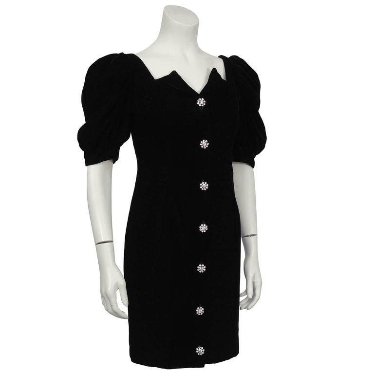 Black velvet cocktail mini dress by Lillie Rubin from the 1980's. The dress has an architectural sweetheart neckline and short puffed sleeves. Large rhinestone buttons fasten up the front with hidden small black snaps for added coverage. Matching