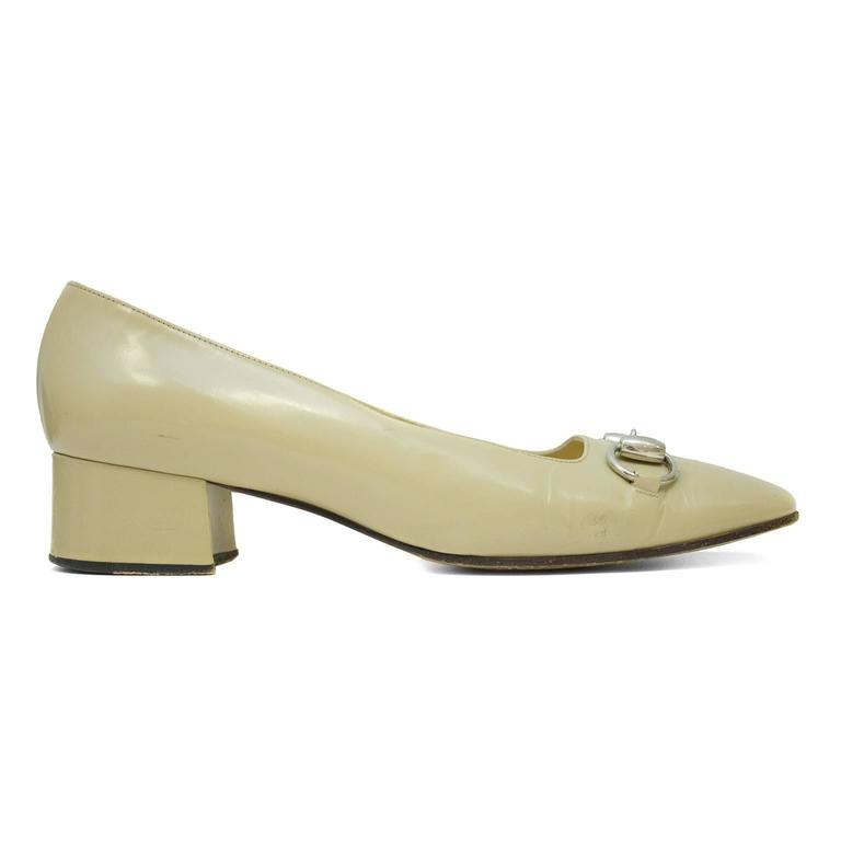 Gucci beige leather low heels from the early 1990's. The have a square toe, chunky leather heel and a silver tone horse bit across the toe box. Minor signs of wear to the soles, marked 71/2 B. In good, vintage condition.