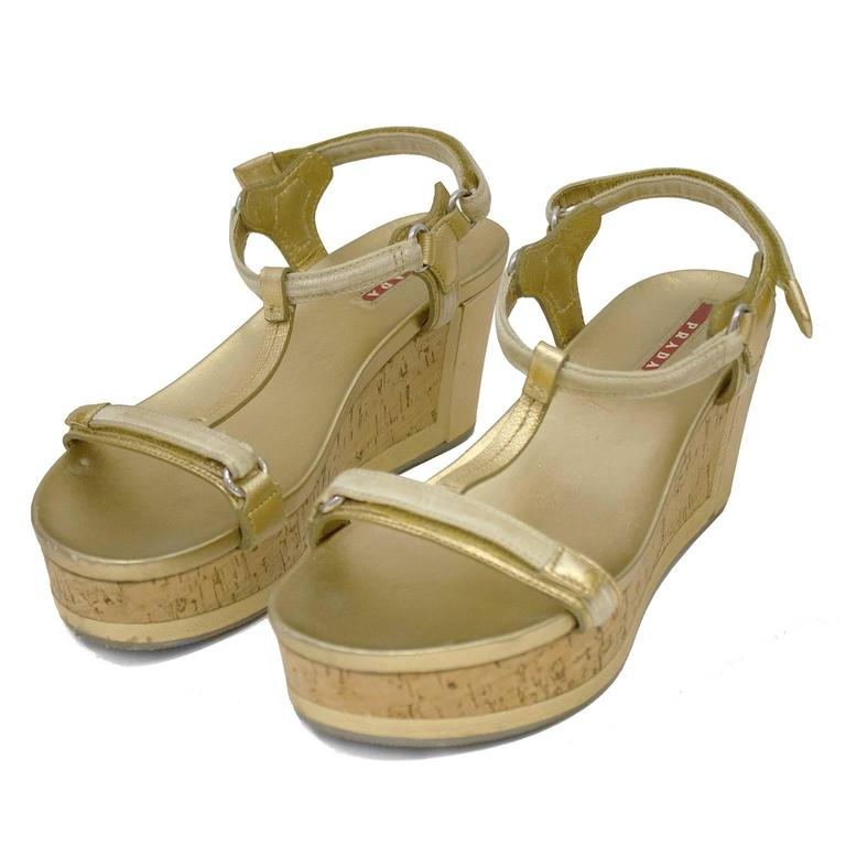 T strap gold leather platform sandals by Prada Sport from the 2000's. The cork sole is accented with a gold leather panel along the heel and the ankle straps fasten with velcro. Cream velvet details along the straps, silver hardware and grey