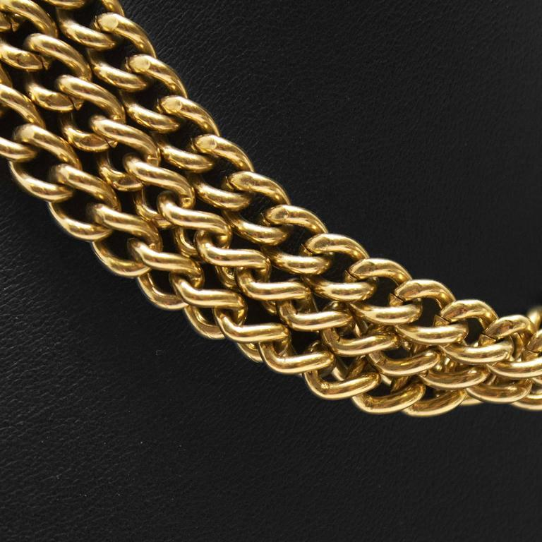 1980's goldotne triple strand chain choker by Givenchy. Fastens with a Givenchy Paris stamped clasp at the nape of the neck. Givenchy authenticity tag underneath clasp. In excellent condition.
