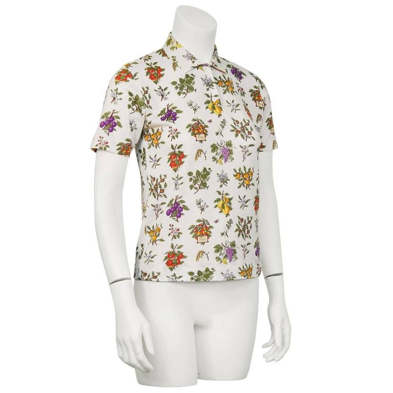 Early 1970's Gucci floral polo top in 100% fine cotton jersey. The look is classic, the fit is petite and the condition is very good vintage. There are some tiny areas of fading but hard to make out. Overall condition very good. Fits like a US size