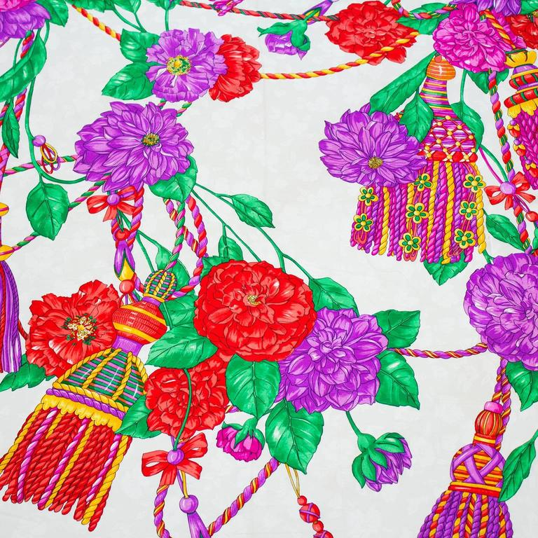 Vibrant colored 1980's silk jacquard scarf by Balenciaga. White background with purple, red, green and yellow floral and tassel design. Black border with white Balenciaga signature. Hand rolled edges. In excellent condition. 35