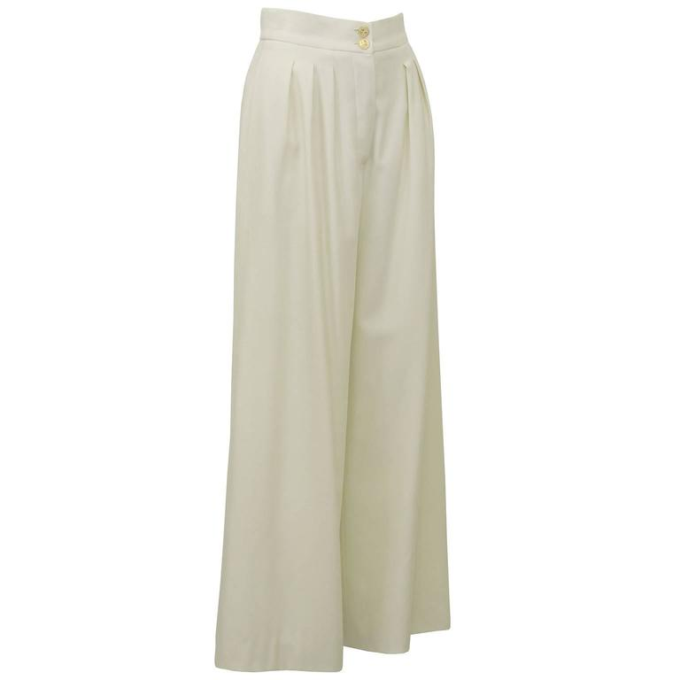1990's high waisted, cream, wide leg Chanel trousers. Stunning cut and shape with the most classic gold four leaf clover Chanel buttons, in perfect condition. Mid weight wool for all seasons. Small hole from age and wear on right leg, otherwise
