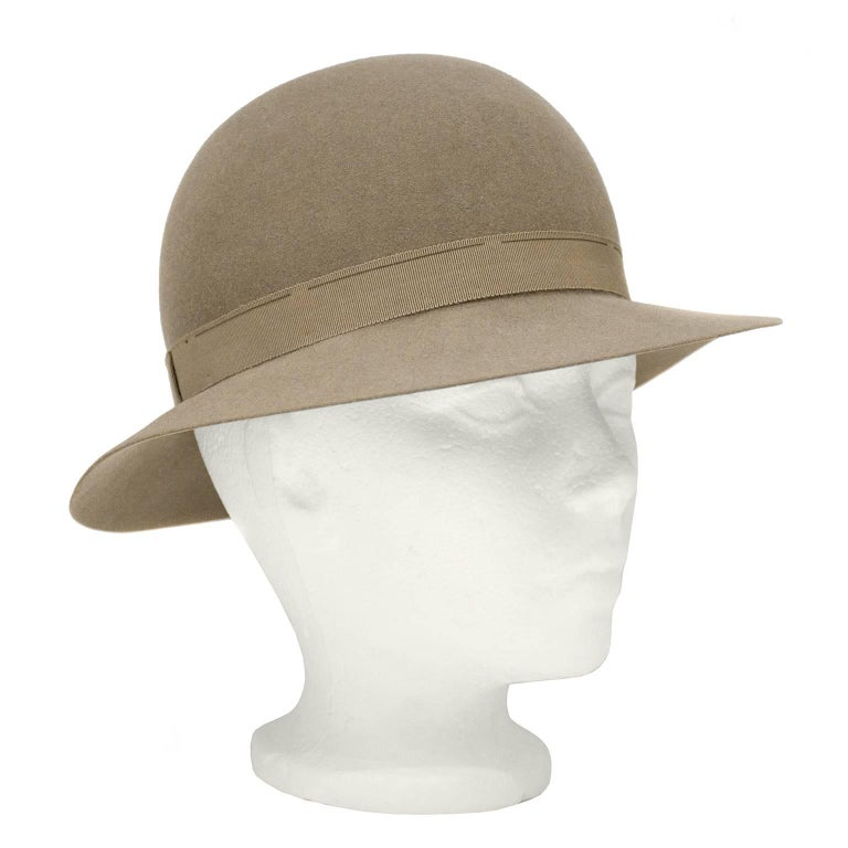 """Darling 1970's Yves Saint Laurent taupe felt bowler hat. Matching taupe grosgrain ribbon trim on exterior and interior. Exterior ribbon features a flat bow. Excellent vintage condition.   Diameter 22.5"""""""