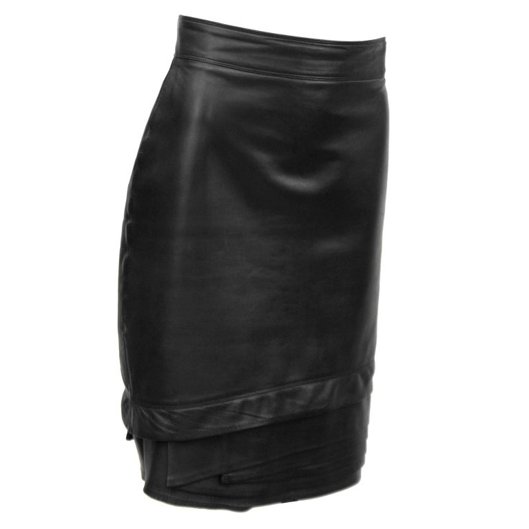 """Black leather Gianni Versace skirt from the 1980s. The skirt has a banded waist and a beautiful tiered detail on the hem. Back zip, fully lined. In excellent condition.   Waist 28"""" Hips 34.5"""" Length 23"""""""