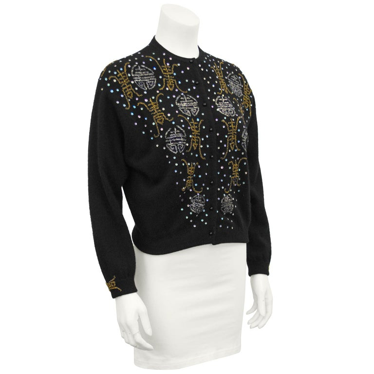 Elise Tu Hong Kong label black beaded cashmere sweater from the 1950s. Decorated down the front, along the back of the neck and on the cuffs with silver and gold beads resembling Chinese characters. Flat iridescent sequins scattered throughout. In