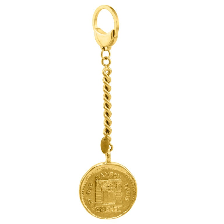 Chanel keychain dated from collection 23. The goldtone coin is stamped with the iconic Rue Cambon address and image. Rounded chainlink connects the coin to the key ring. In excellent condition.  No original box.