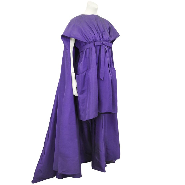 Roberto Capucci deep purple silk cocktail dress from the late 1950s. The short hemline is countered by a long and flowing cape attachment from the shoulders that billows behind when worn. The boat style neckline allows for the cape to cover the